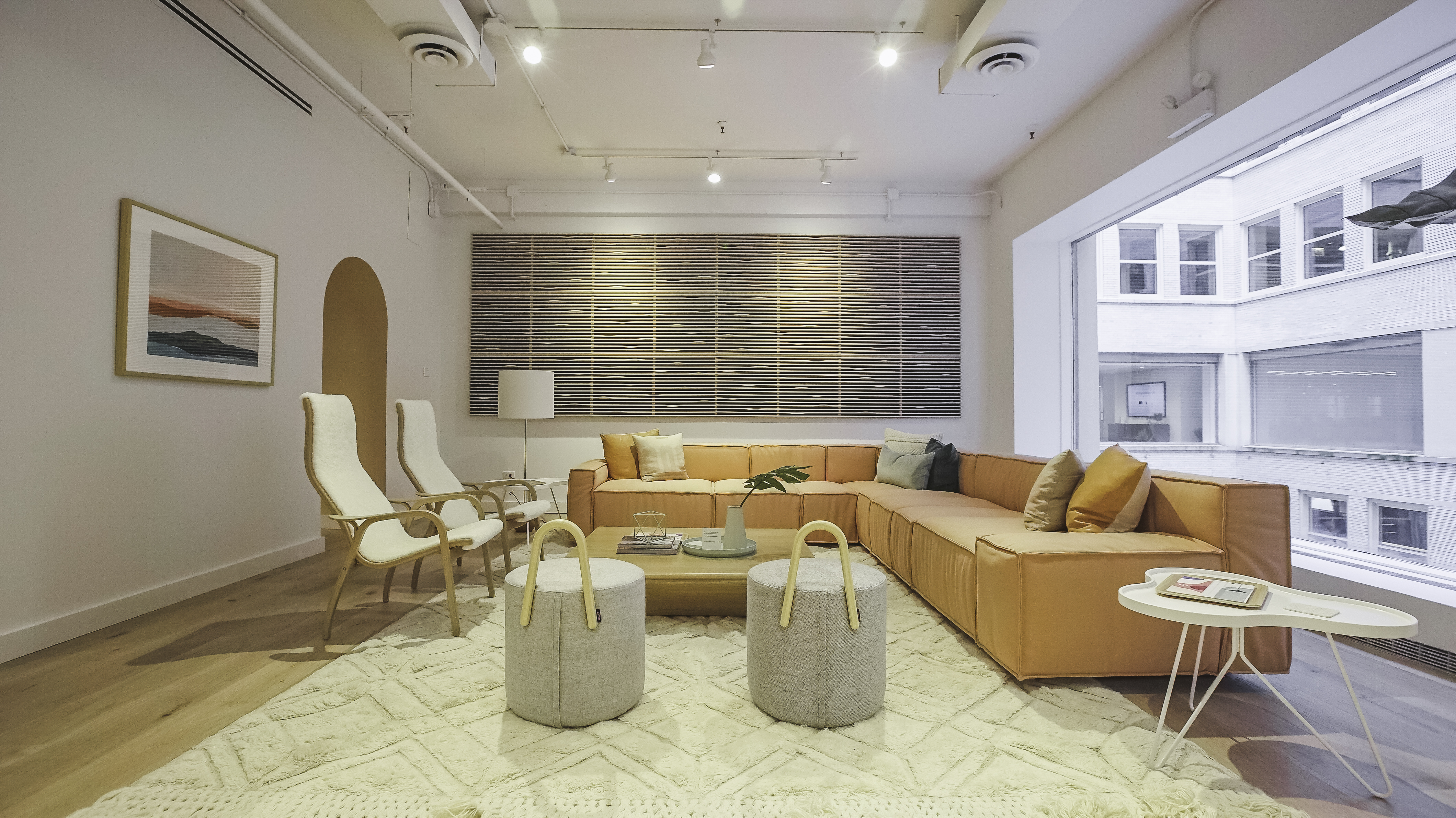Image of Hightower's showroom with a pale peach colored sectional, two Lamino chairs with white sheepskin, and two Amstelle Poufs. The room has a white rug and wood floors.