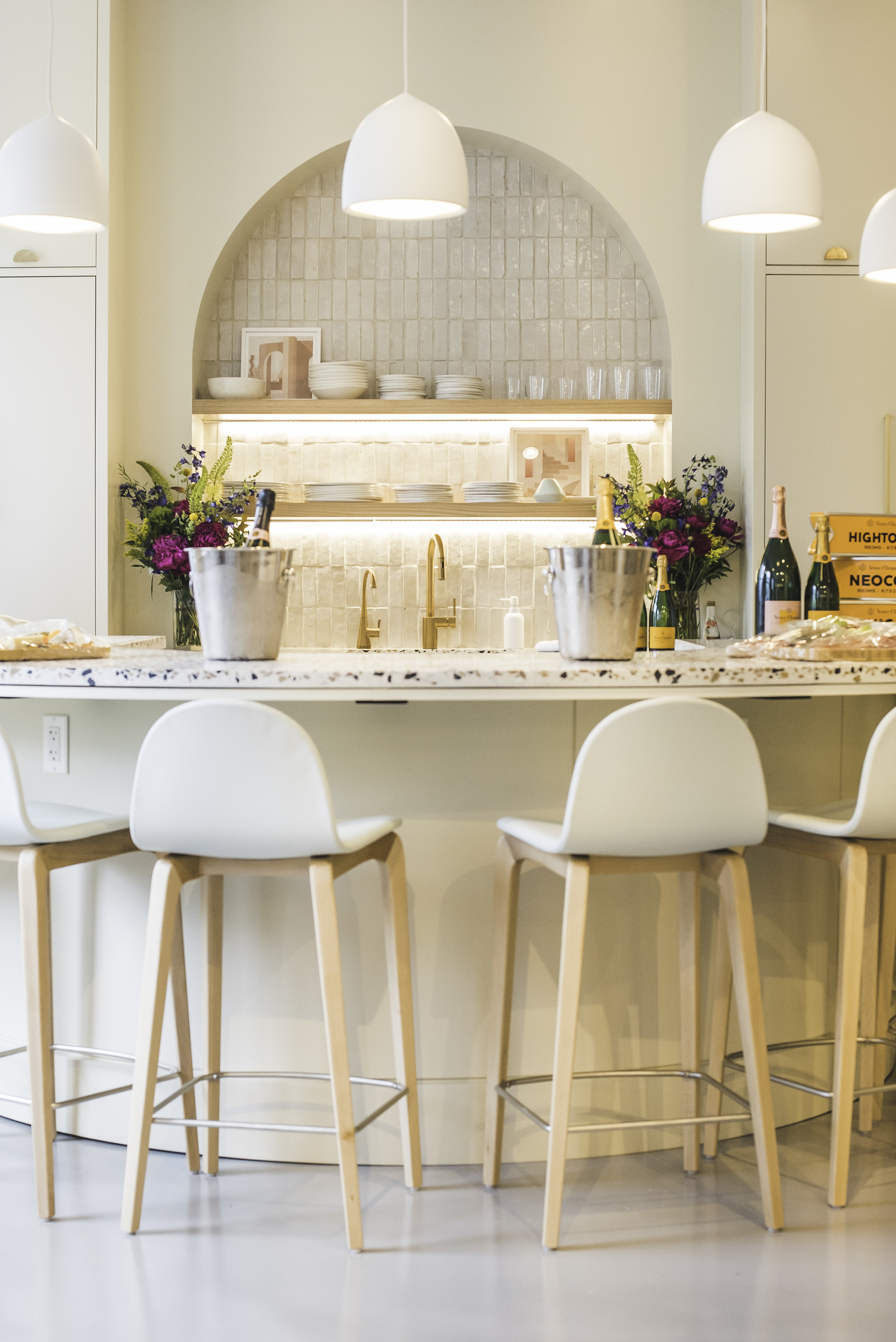 Image of Hightower's showroom kitchen. The kitchen has a rounded bar and an arched alcove behind the sink. There are barstools around the bar and white pendants above.