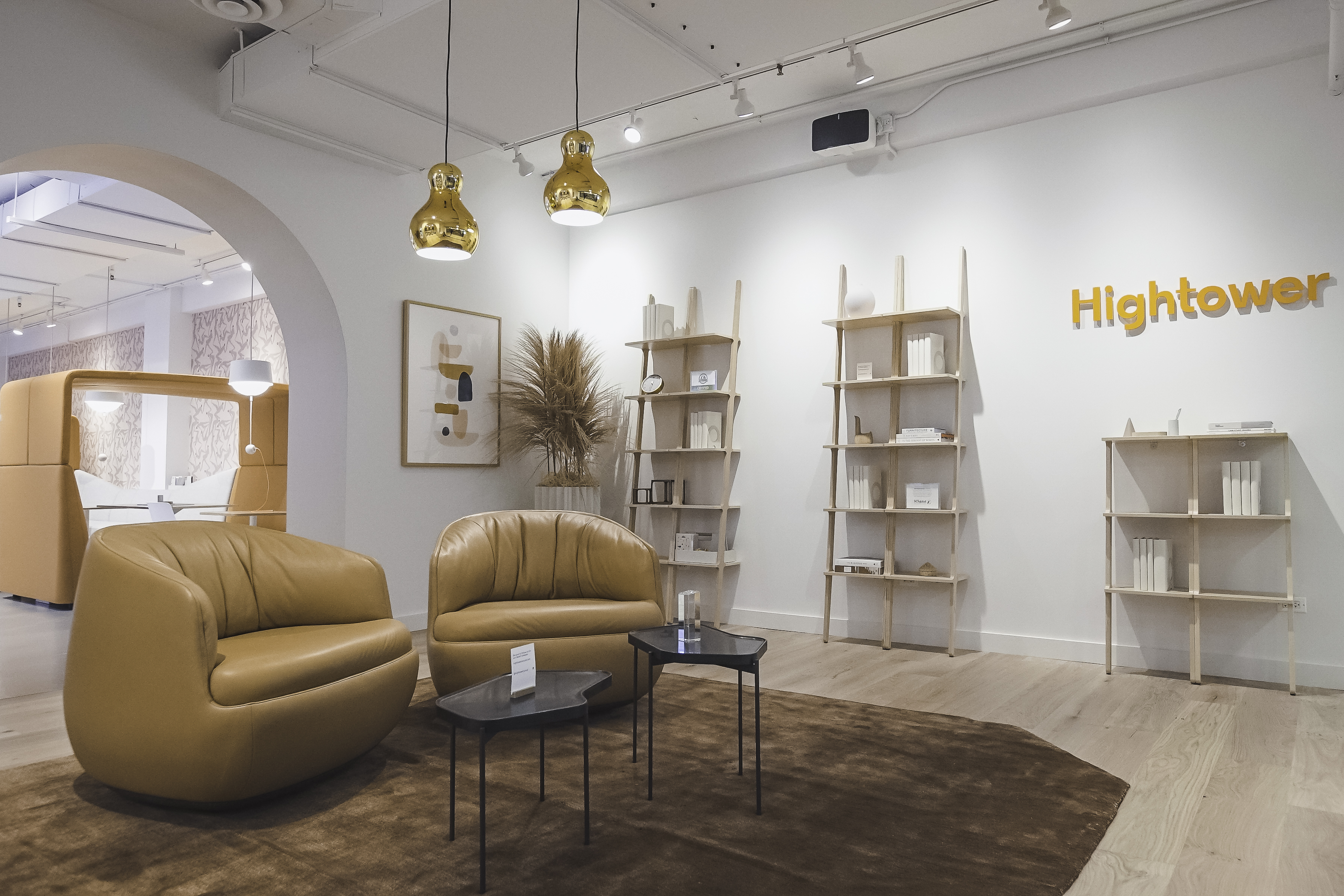 Image of the entry to Hightower's showroom. The room includes three sets of Libri Bookshelves, two Gimbal Lowback Rockers, two Pond Tables, and two gold Calabash Pendants.